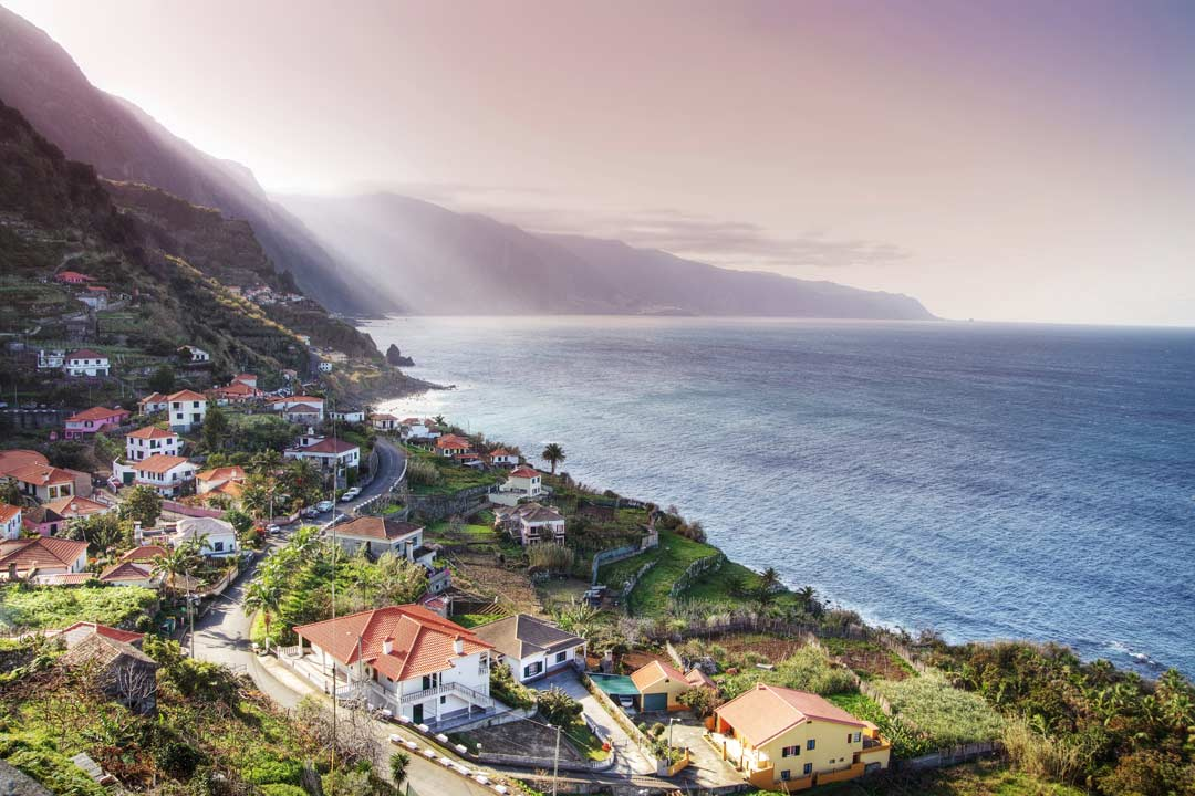 A view along the coast, with a village along the hillside and the misty ocean to the right