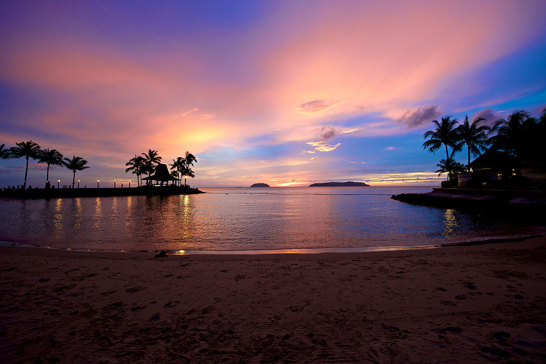 A beautiful purple and pink sky over calm waters and golden sands