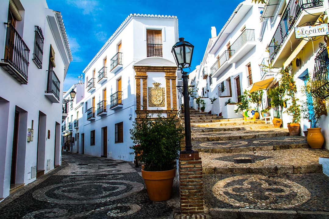 a colourful street with bright white houses, patterned cobbled floors and greenery