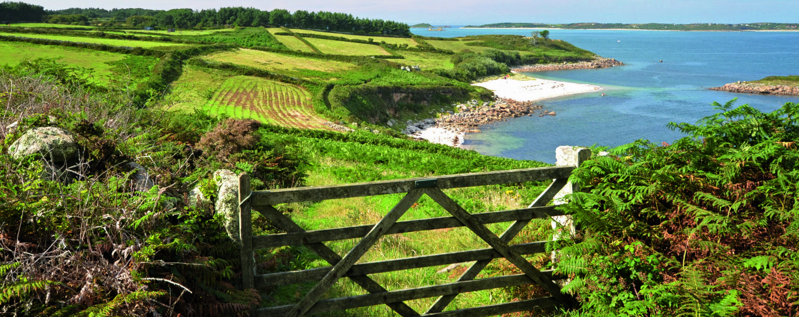 A wooden gate leads to green fields overlooking clear blue waters and white sand beaches