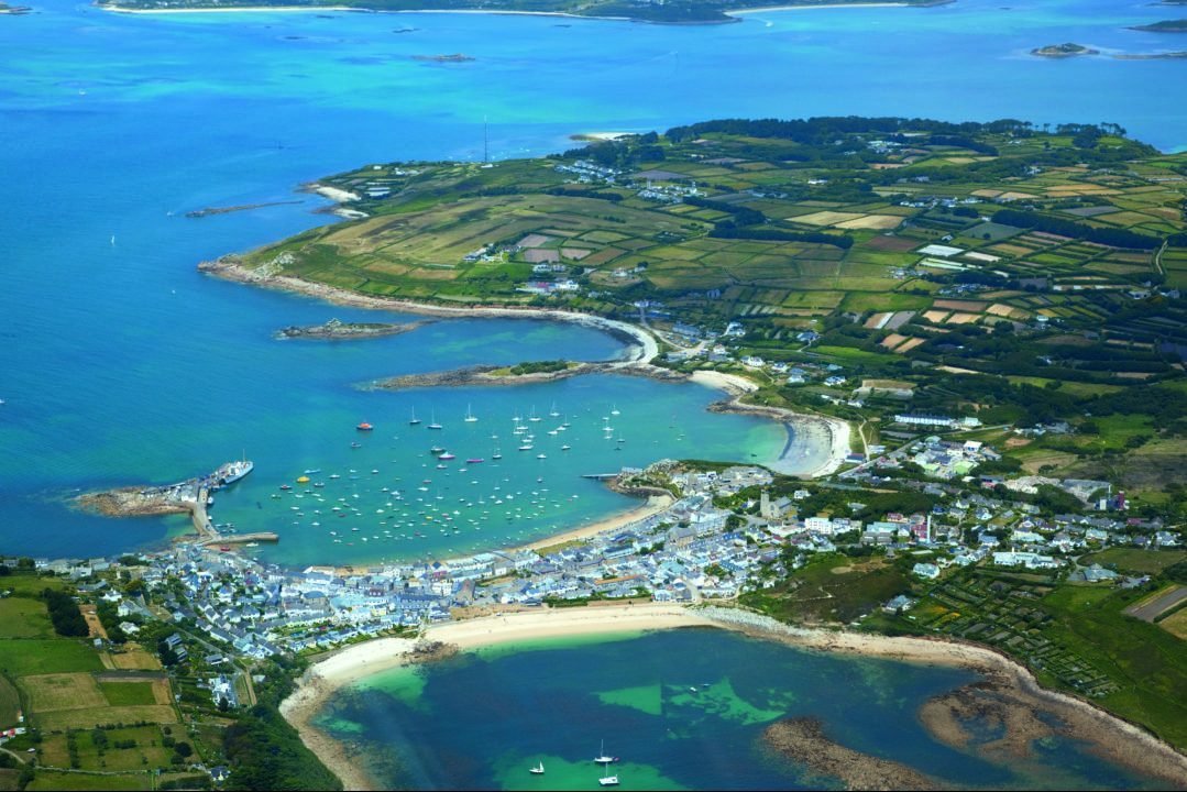 An aerial view of St Mary's Island showing a patchwork of fields and white sandy beaches