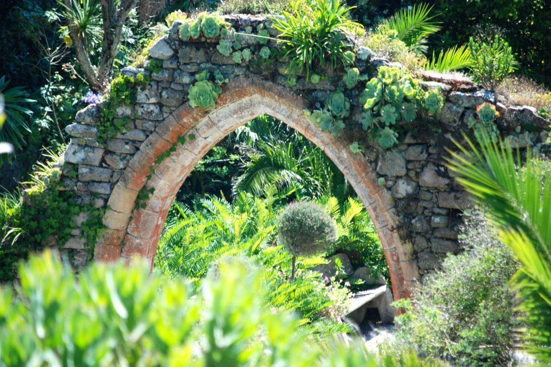 The old archway of Tresco Abbey covered in tropical plants
