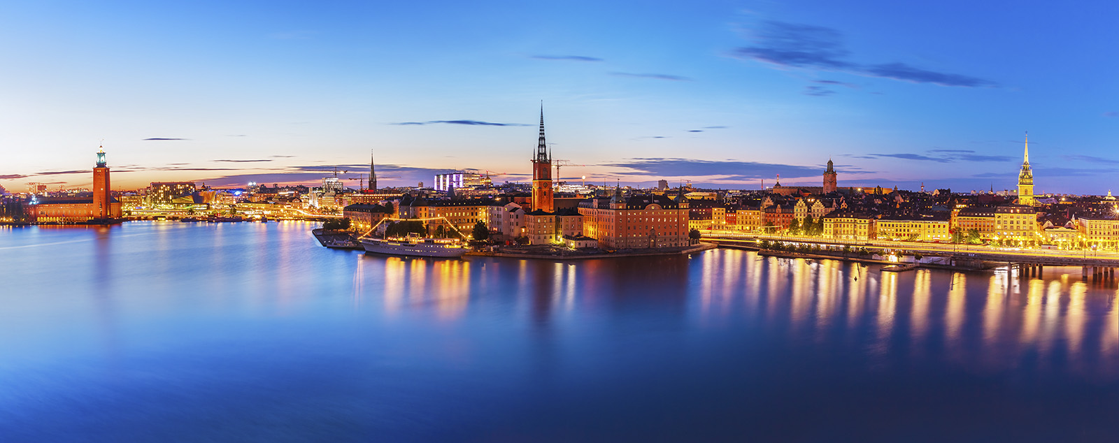 The lights of Stockholm's old town glowing and reflecting off the water in the twilight hours.