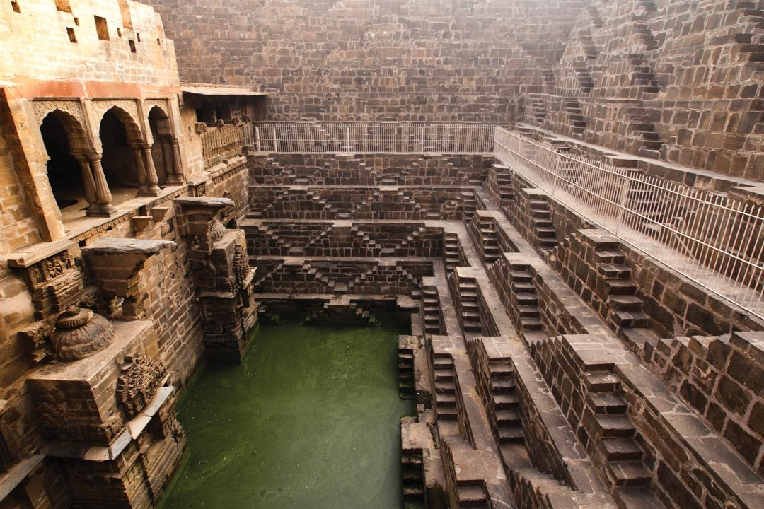 A monumental stepwell leading down to a pool of water