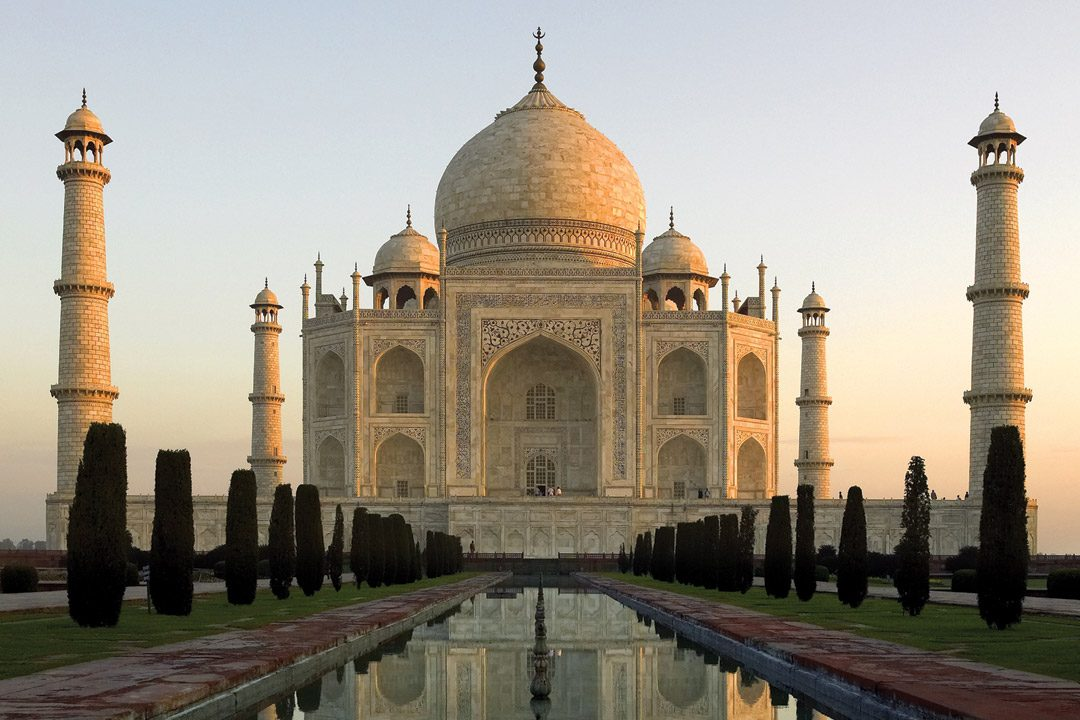 The white domed Taj Mahal surrounded by 4 minarets with formal gardens and lakes leading to it