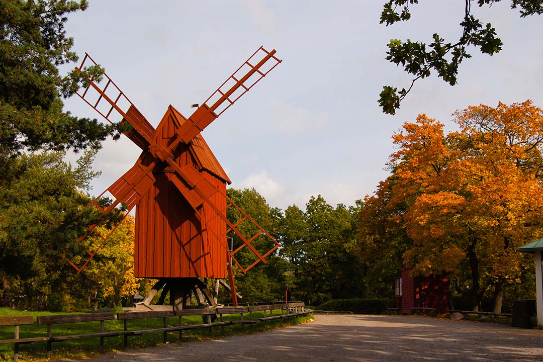 A traditional Swedish windmill surrounded by lush green trees in the Skansen open-air museum.