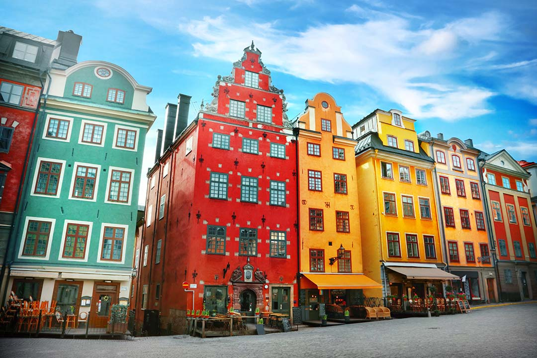 Bright and contrasting colourful buildings hosting cafes with outdoor seating areas line Stortorget place in Gamla stan, the old town.