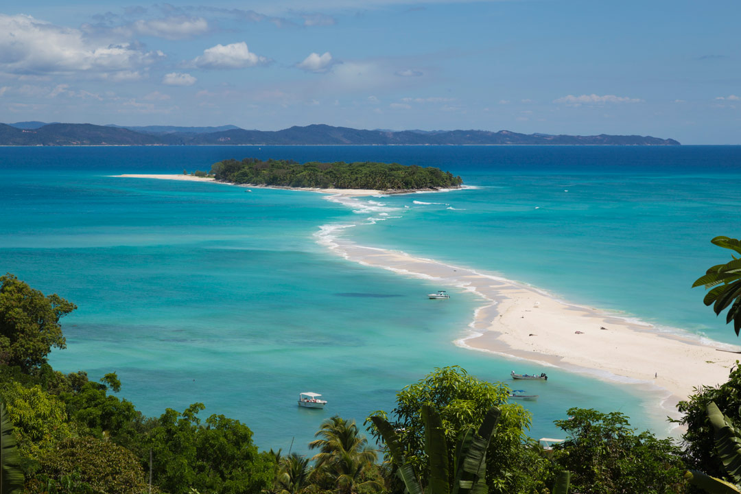A small tropical island with a white sand beach is surrounded by pure blue sea