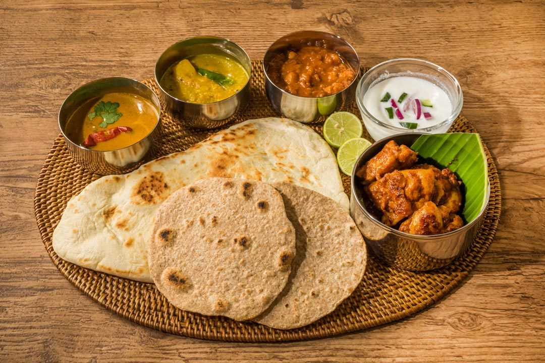 An Indian meal laid out with raita, chutneys, condiments, chapattis, naan bread and lime