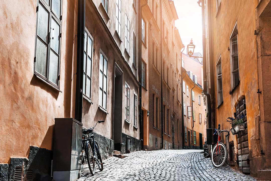 Sunlight breaks through onto the cobbled, empty and narrow street of Gamla Stan, the old town. Bikes sit against the uneven walls of homes that have been standing for many years.
