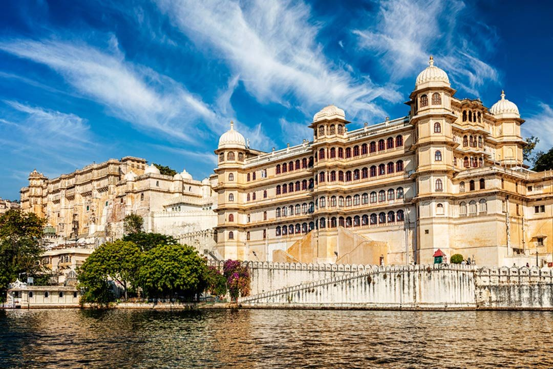 A large yellow palace in Udaipur next to a lake