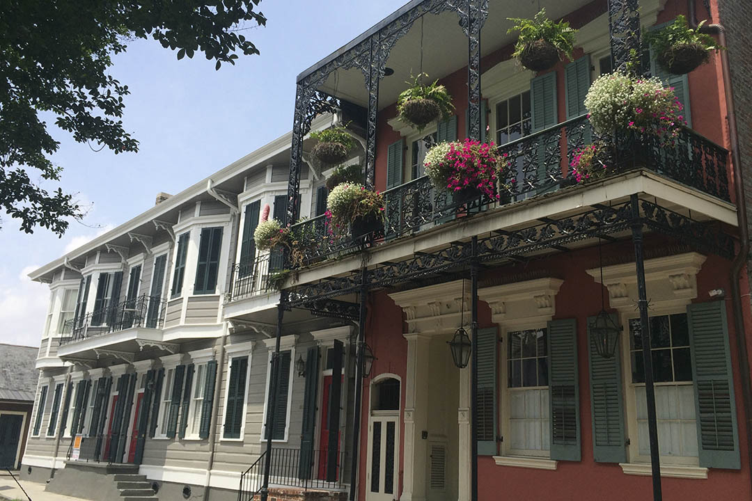 Ornate balcony and hanging baskets on traditional New Orleans' town houses