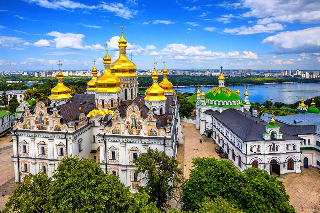 Kyiv Monastery of the Caves, a white grand building with grey tirmmings and bright golden yellow bulb roofs.