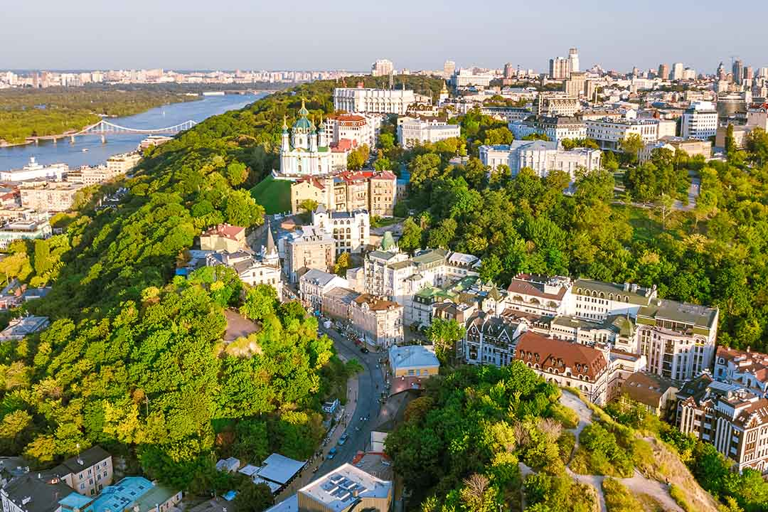Aerial top view of Saint Andrew's church and Andreevska street from above, cityscape of Podol district on sunset, city of Kiev