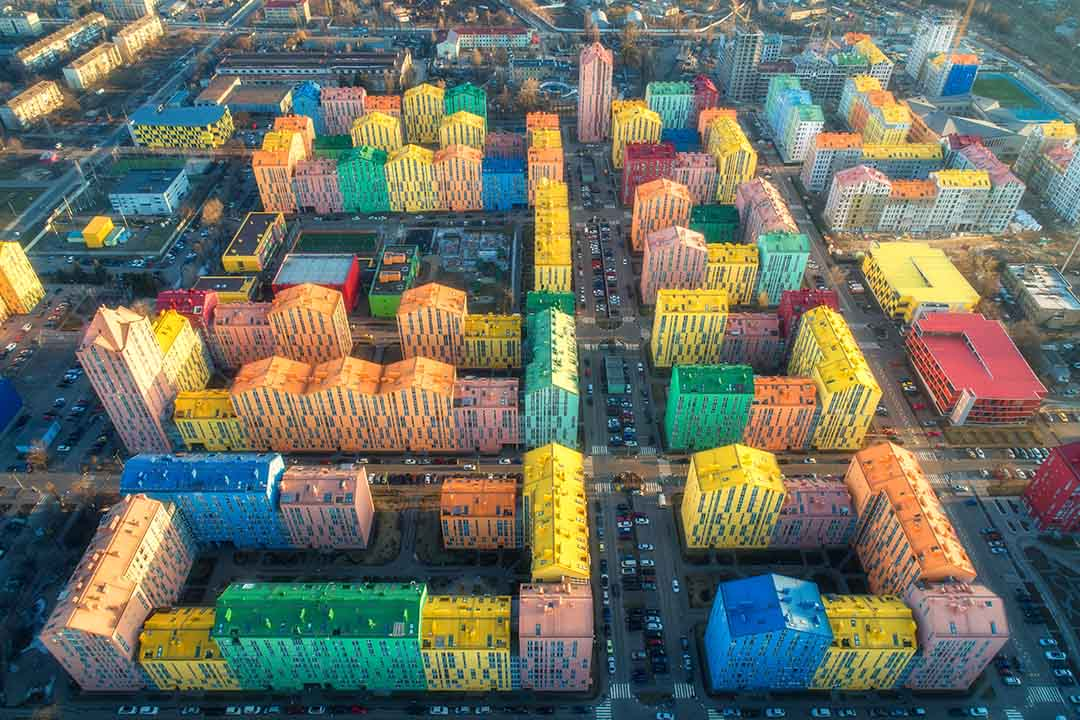 Aerial view of the colorful buildings in european city at sunset. Cityscape with multicolored houses, cars on the street in Kiev, Ukraine.