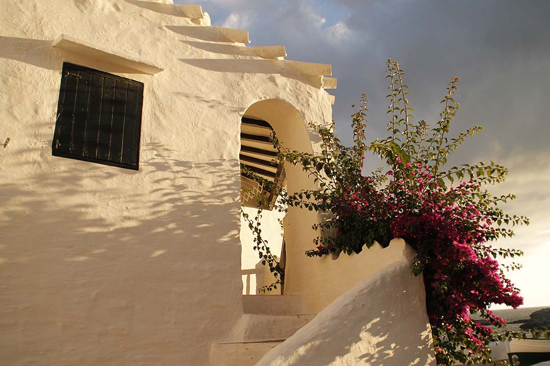 Entrance to the covered porch in old village of Binibeca Vell in Menorca in warm day at sunset.