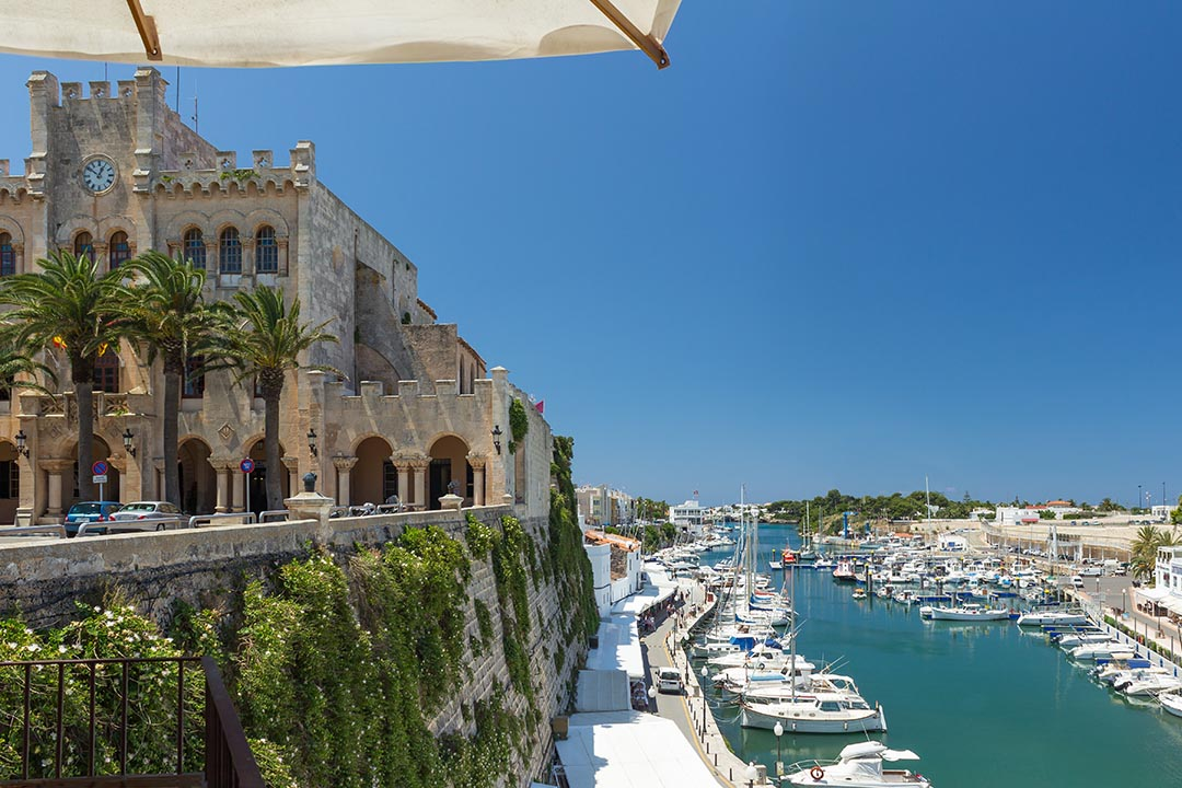A view across the harbour in Ciutadella. A large and grand building stands over looking boats bobbing in the water