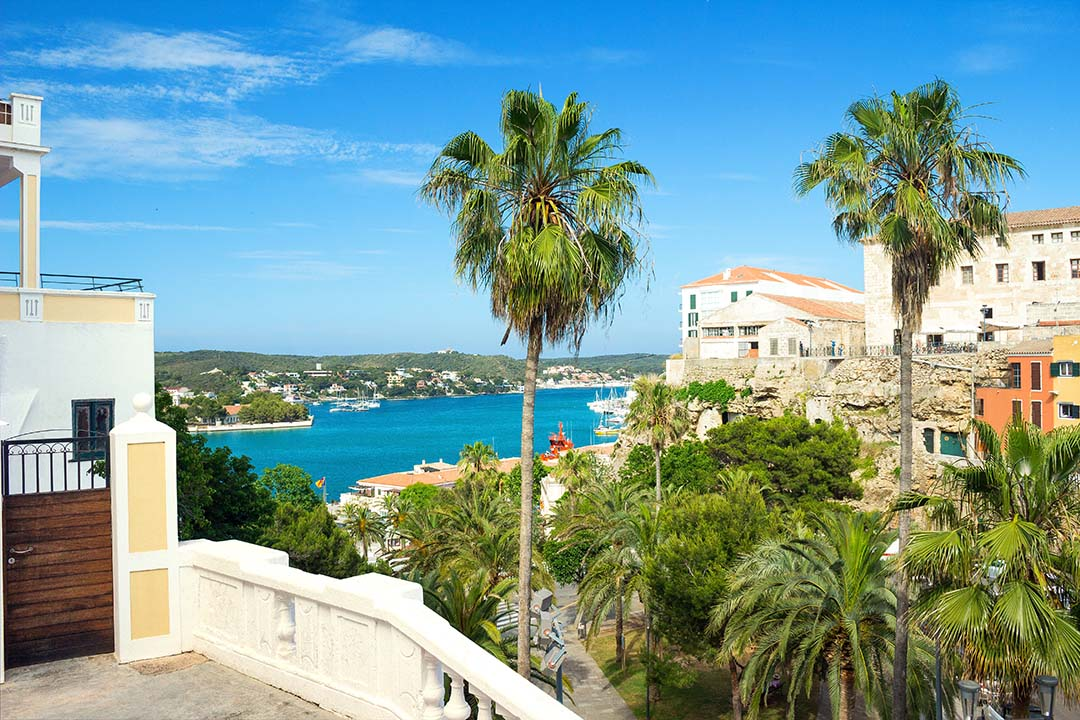Mahon, Menorca, view to the harbour. Palm trees coat the land and the vibrant blue sea can be seen in the distance