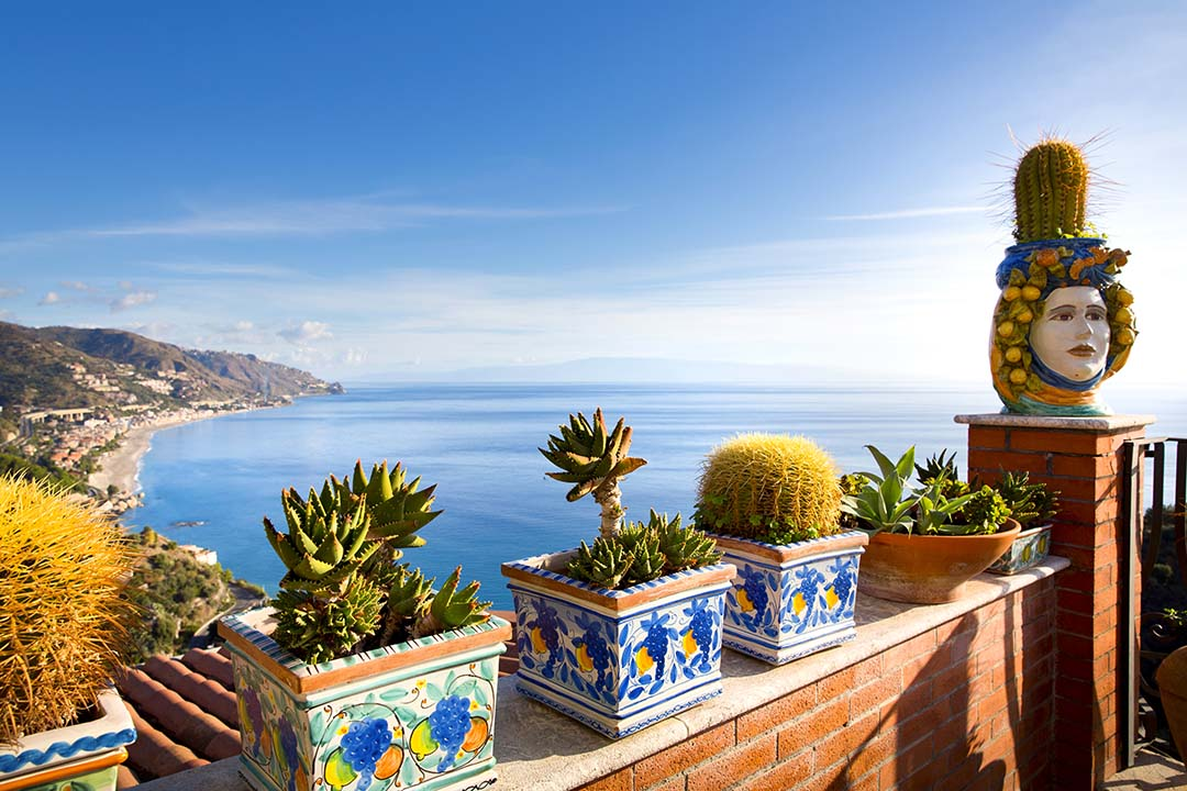 The coastline of Toarmina can be seen behind cacti in mosaic plant pots balanced atop a wall