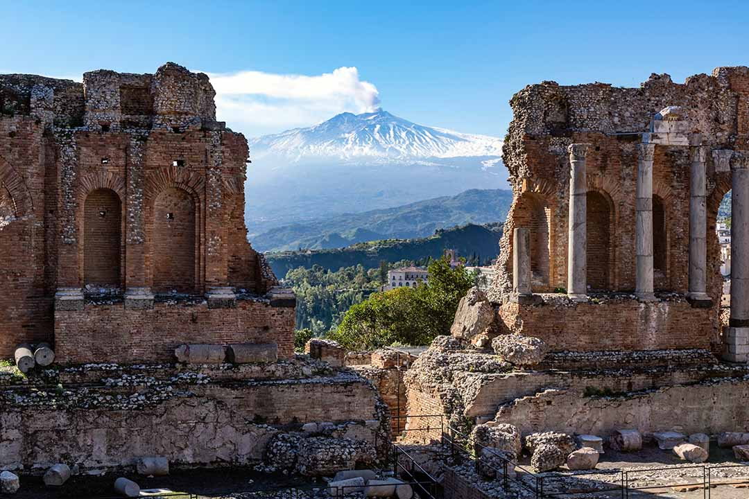 Volcano Etna in Sicily seen through ruins of ancient amphitheater in Taormina