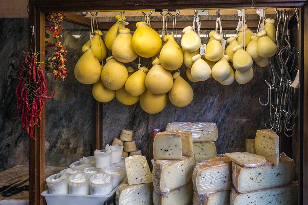 Cheese shop with large selection of cheeses in Sicily. Bulb shaped cheeses hang from the ceiling with an array of different cheeses below.