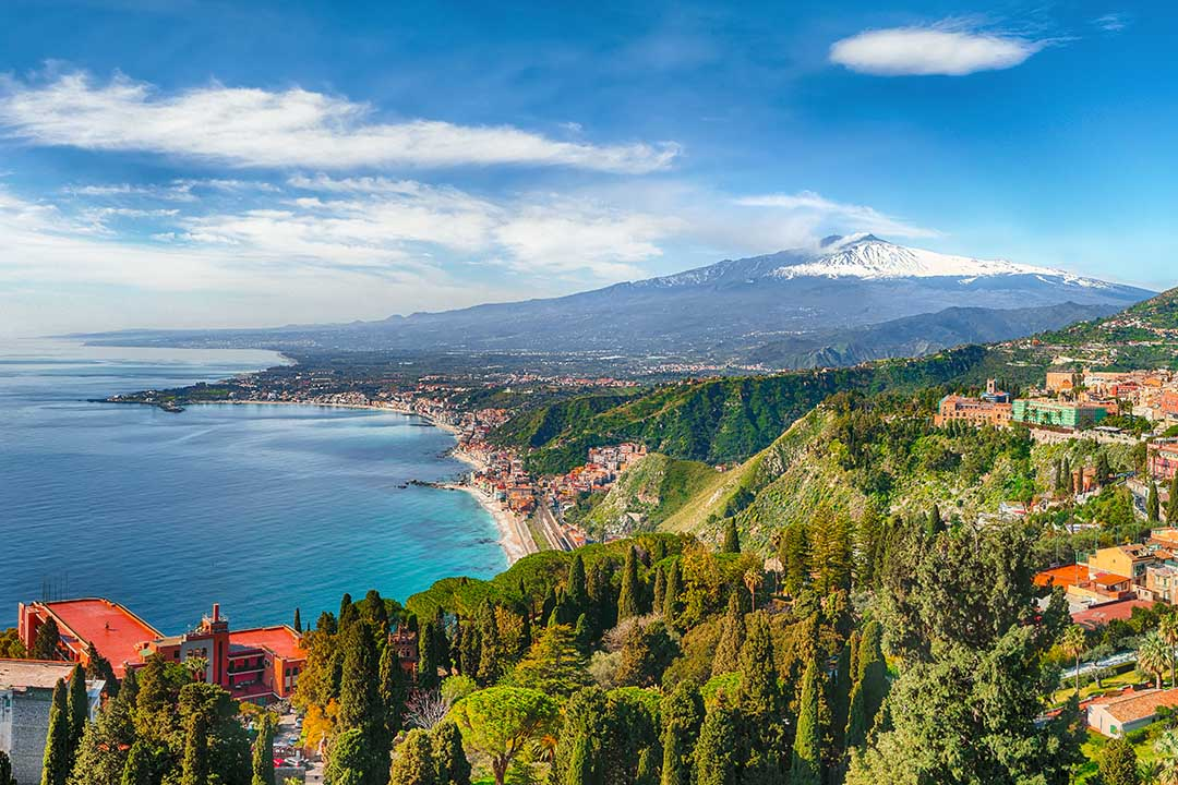 A view of the coastline of Taormina, the land is coated with thick green fauna and Mt Etna can be seen in the background, towering over the landscape