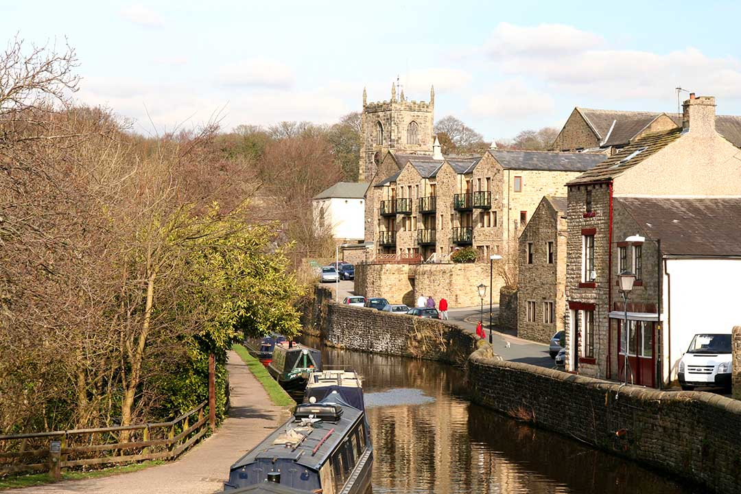 A branch of the Leeds Liverpool Canal runs alonside the stone buildings in Skipton in the Yorkshire Dales.