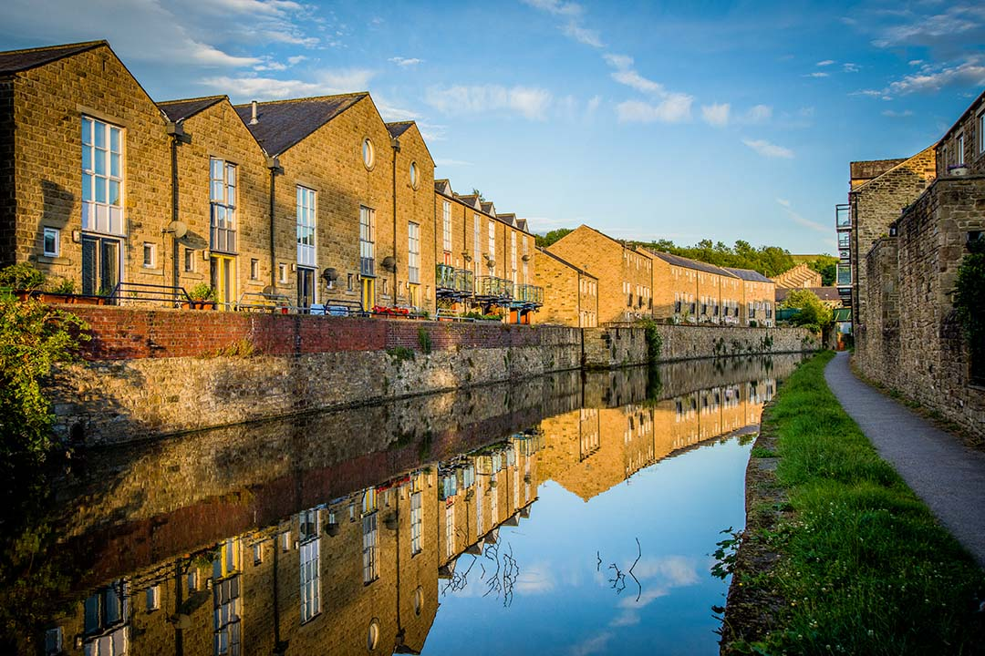 A row of brickwork buildings sit alongside still canal waters. They are reflected on the calm water, with a blue sky shining overhead