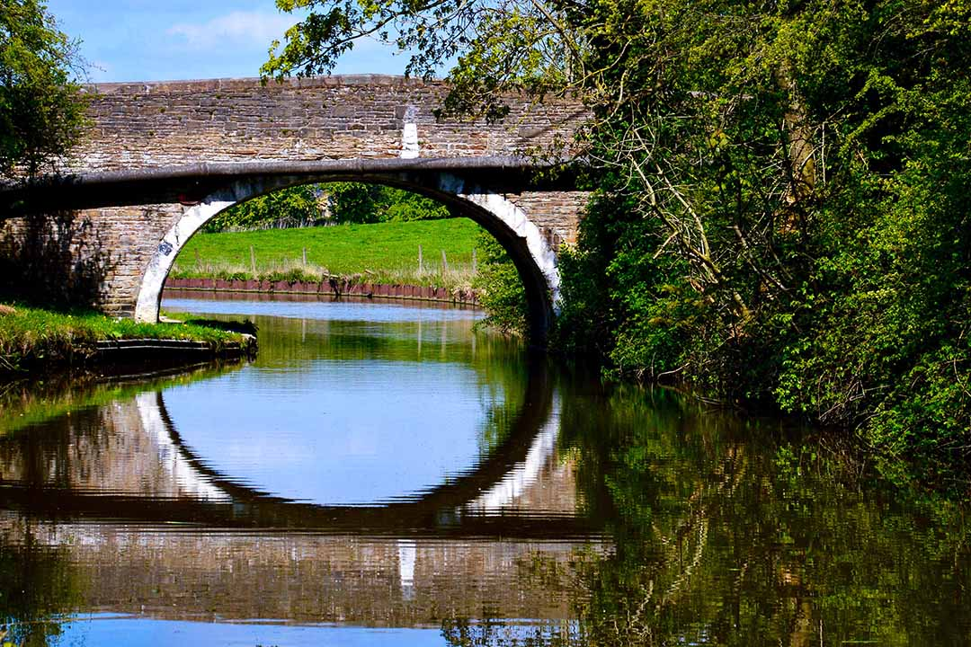 An old stone bridge over still canal waters, at the edge of the water green foliage and grass can be seen