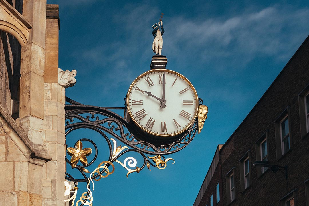 A large ornate clock on the exterior of a building in York. The clock is painted with black and gold trimmings